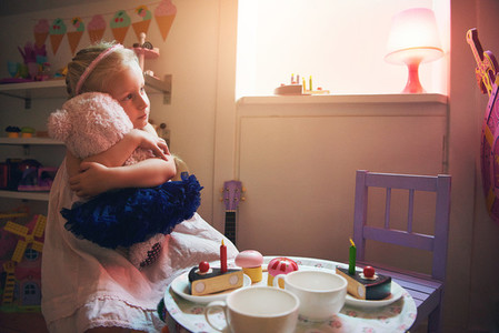 Girl hugging toy bear while tea party play