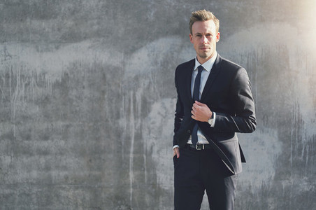 Adult businessman standing at the gray wall