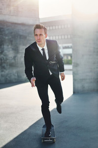 Young businessman in riding skateboard at street