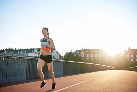 Cheerful woman running along city bridge