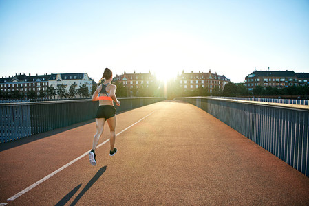 Rear view of athlete jogging toward bright sun