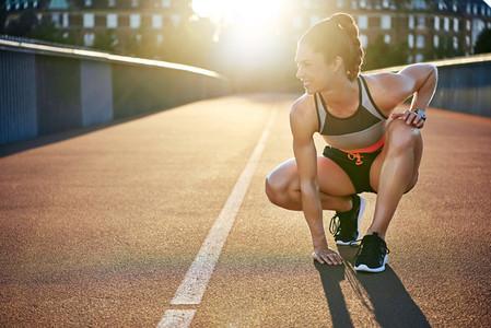 Athletic woman prepares to run as she kneels