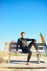Relaxed surfer waiting on a wooden bench