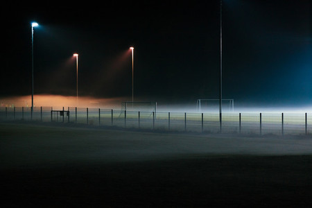 Lonely and mystic football field covered by fog at night