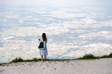 Back view of Young redhead  standing on the path looking towards the valley from the mountain
