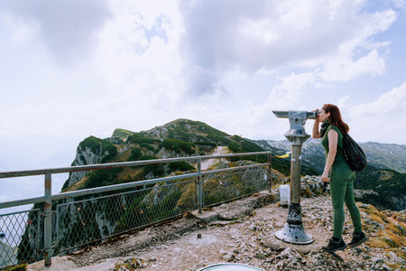 Young redhead woman viewing the mountains and sunset in Coin Operated Binocular viewer traveler