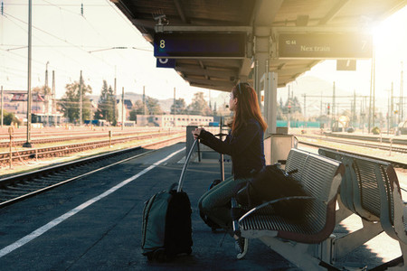 Young redhead woman waiting next train in the station