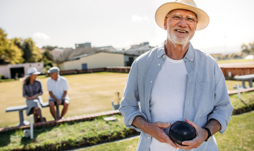 Close up of a man playing boules in a lawn