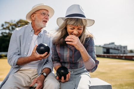 Elderly couple having fun sitting at a park holding boules