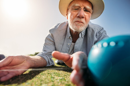 Senior man measuring the distance between boules