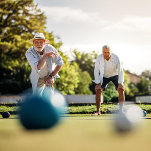 Senior man throwing a boules standing in position