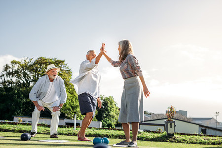 Senior people playing a game of boules in a park