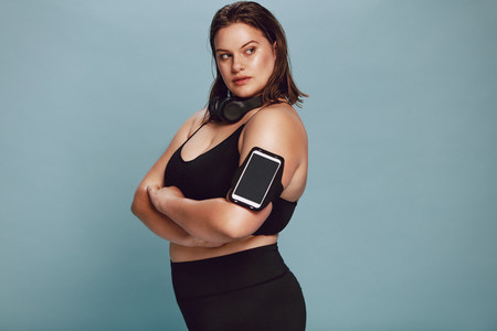 Confident overweight female in sports gear