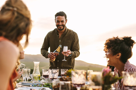 Smiling man serving champagne to friends at party