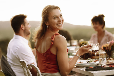 Beautiful woman having food with friends at party