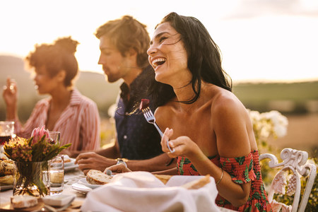 Woman enjoying with friends at outdoor dinner party