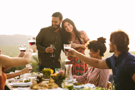 Friends raising a toast for pregnant couple at party