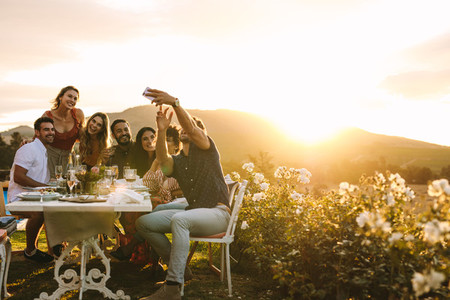 Group selfie at outdoor dinner party