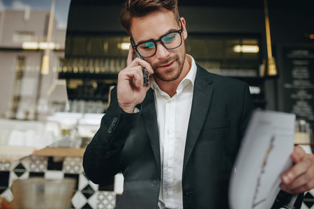 Entrepreneur talking on cell phone looking at office papers in a