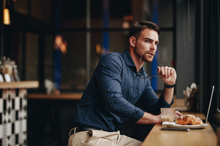 Businessman sitting in a restaurant working on laptop