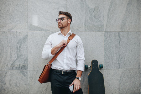 Businessman standing against a wall with a longboard
