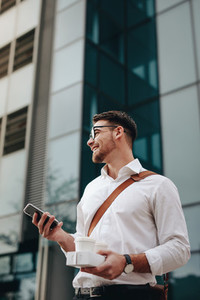 Businessman going to office holding mobile phone and coffee