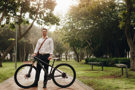 Man standing in park with his bike