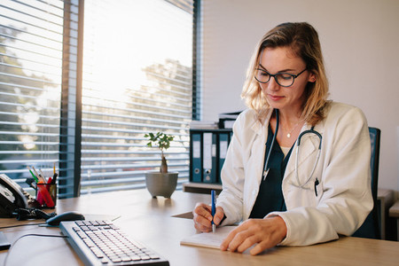 Female doctor sitting at the desk and writing