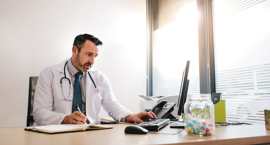 Doctor working at his clinic desk