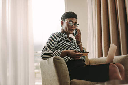 Businesswoman doing online payments from hotel room
