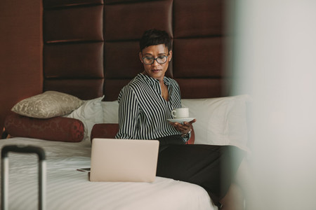 Businesswoman in hotel room with laptop and coffee