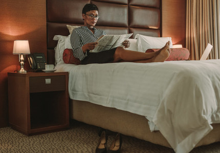 Mature businesswoman relaxing on hotel room bed with newspaper