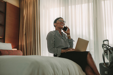 Woman CEO on business trip working from hotel room