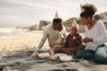 Family celebrating birthday of their son at the beach