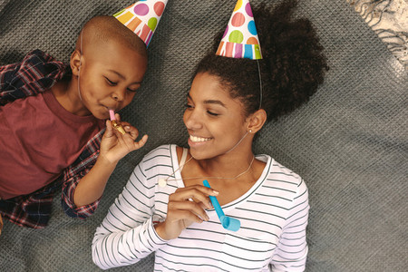 Mother and son with party hats blowing whistles