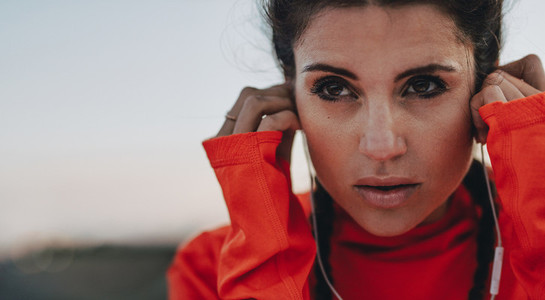 Female runner adjusting her earphones