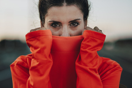 Sportswoman covering her face with tracksuit