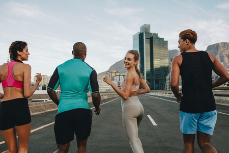 Female running with friends outdoors in the city
