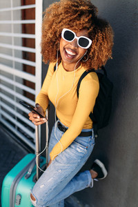 Cheerful woman traveller in sunglasses with a trolley bag