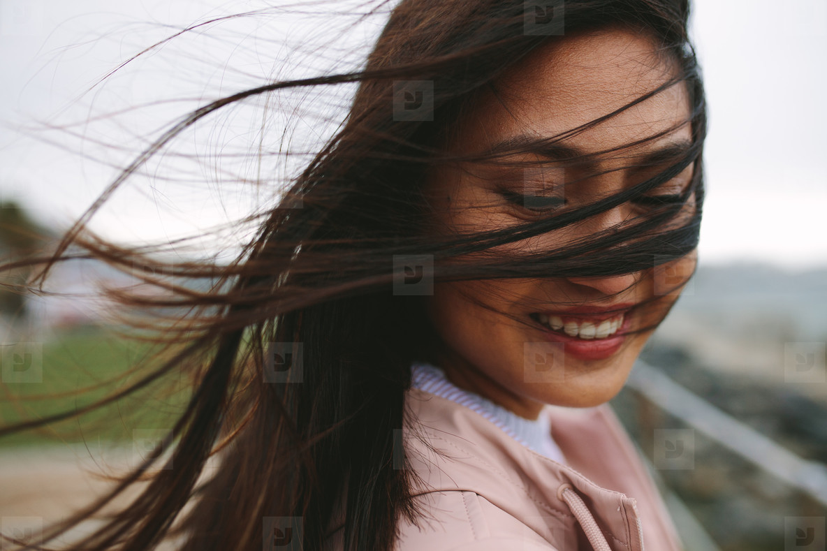 Close up of a smiling woman with her hair flying on her face