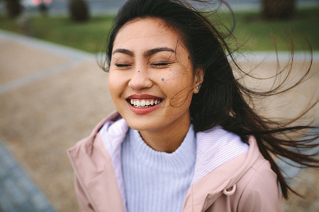 Close up of a smiling asian woman standing outdoors