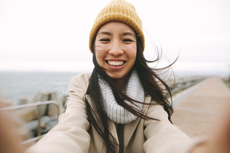 Close up of a smiling woman in winter wear standing near the sea