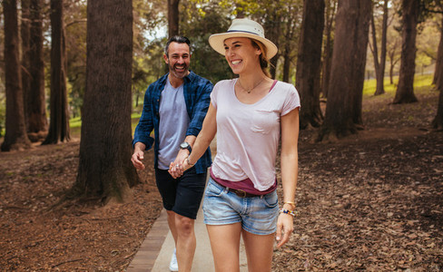Beautiful couple walking through park and smiling