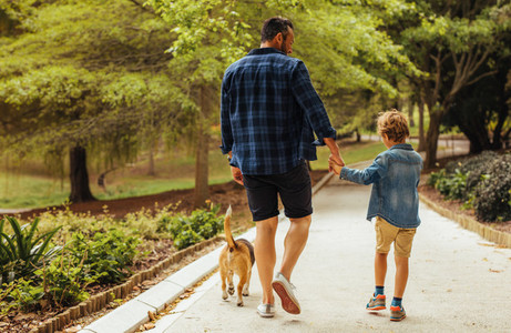 Father and son walking with a dog in the park
