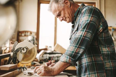 Senior carpenter planning his work at carpentry