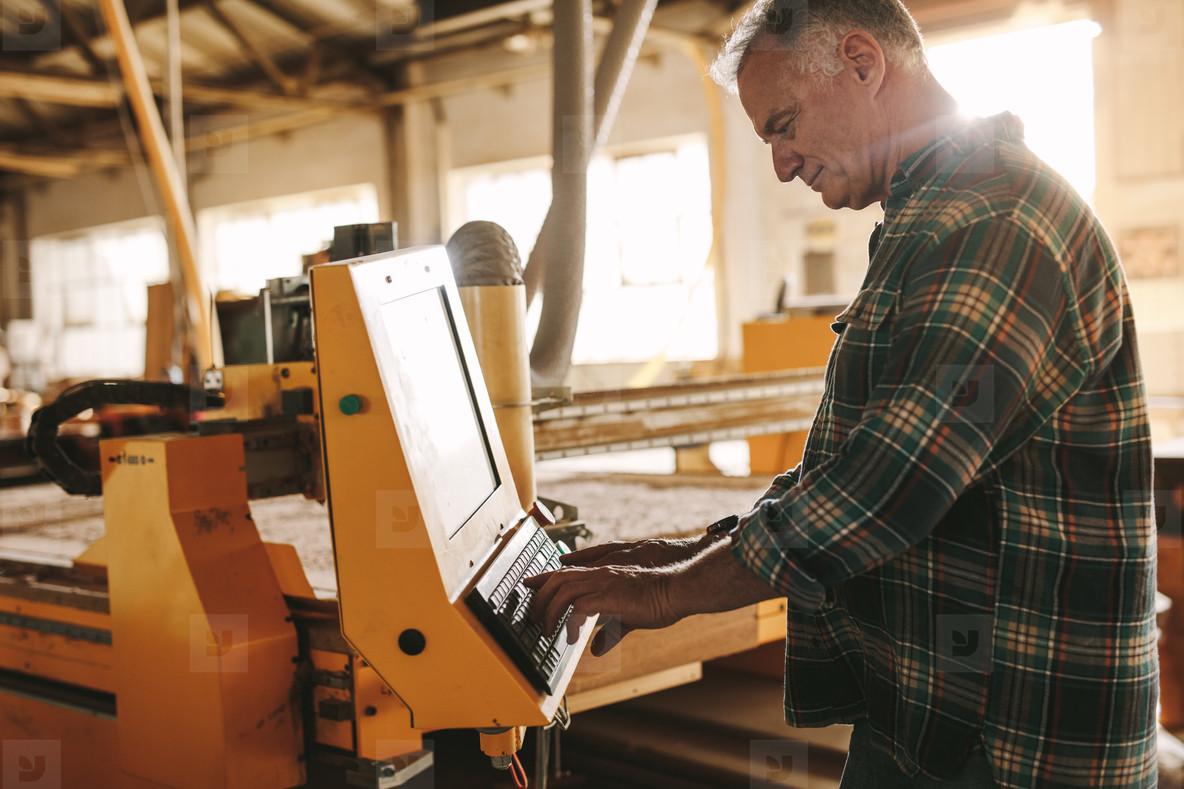Carpenter programming a cnc wood working machine