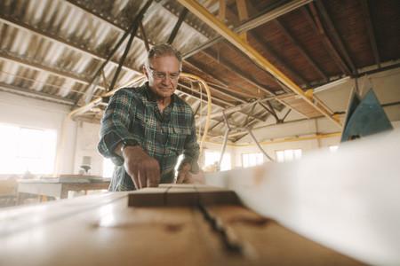 Senior male carpenter working in carpentry workshop