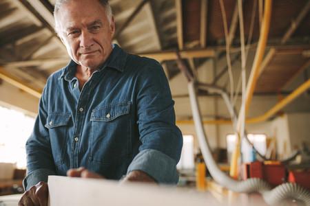 Senior carpenter inspecting the wooden bar