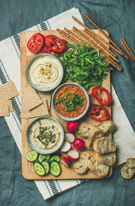 Vegetarian dips hummus babaganush muhammara on wooden board