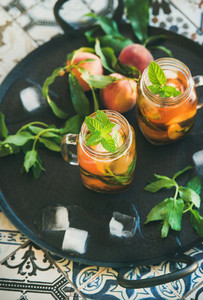 Summer refreshing cold peach ice tea in glass jars